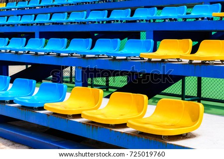 Empty Tennis Court Chairs.Row Of Seats In Tennis Court. Blue And Yellow  Chairs