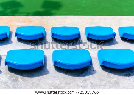 Empty Tennis Court Chairs.Row Of Seats In Tennis Court. Blue Chairs In A