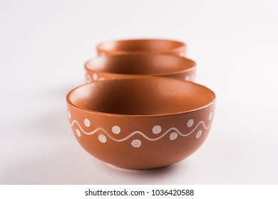 Empty terracotta bowl or brown clay serving bowl isolated on white