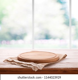 Empty textured wooden pizza board with napkin on the table and kitchen window blurred background. Top view mock up. Selective focus.