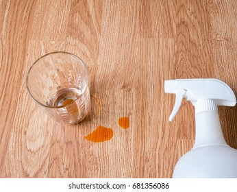 Empty Thai milk tea glass with stain on wooden background comes with spray bottle, cleaning concept