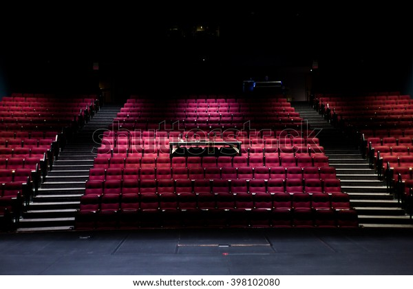 Empty theater with red chairs at a musical stage, before or after an audition.