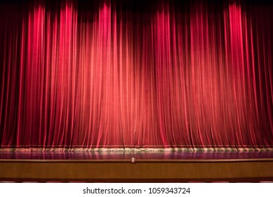 Empty theatre stage and red curtain or drapes background.