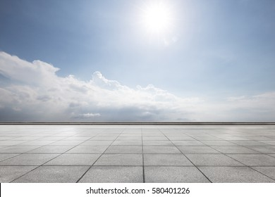empty tile floor in blue sunny sky