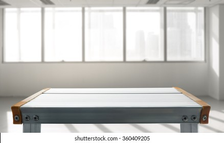 Empty the top of aluminium table with  blurred white room window background.for product display