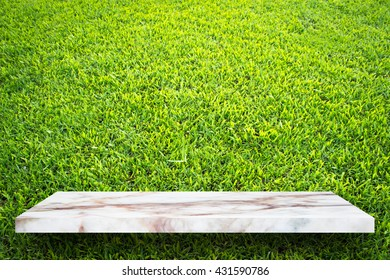 Empty top marble shelves and green grass background / for product display montage product display