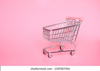 Empty top view mini pink shopping cart  or trolley shopping on pink background, concept shopping in supermarket.