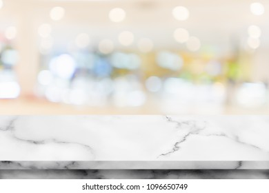 Empty top of white marble table with interior in shopping mall for background.