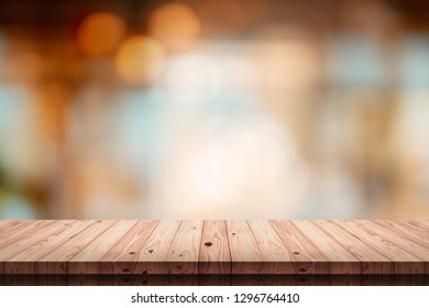 Empty top of wodd table with blur cafe or coffee shop background.