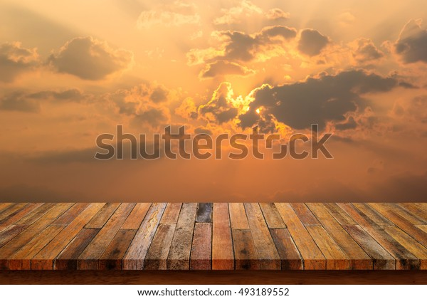 Empty top of wood table with beautiful landscape clouds and the sunset background.