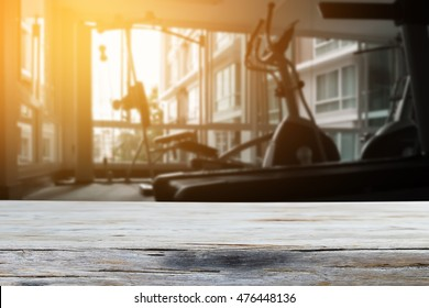 Empty top wood table and blur fitness gym background .Product display template