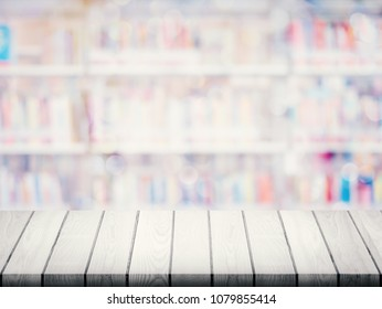 Empty top of wood table with blurred many books on bookshelf in library background.