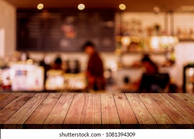 Empty top of wood table with blurred interior in cafe background.