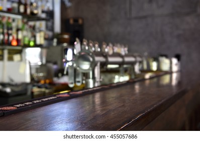 Empty the top of wooden counter bar and blurred bottles. Background for your product display