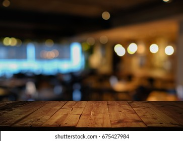 Empty top of wooden table with abstract background of blurred cafe restaurant, coffee shop with bokeh light background. - can be used for display your products.