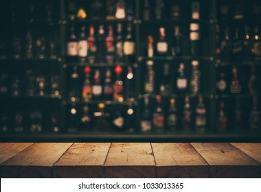 Empty the top of wooden table with blurred counter bar and bottles Background /For montage product display or design key visual layout.