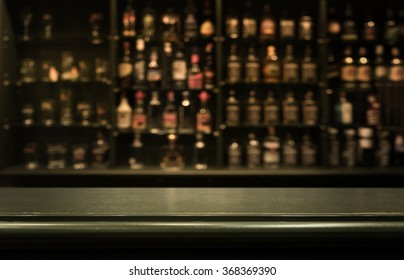 Empty the top of wooden table with  blurred counter bar and  bottles Background /for your product display
