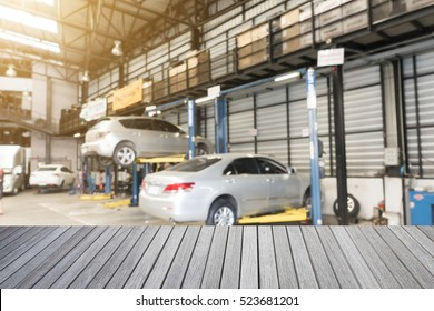 Empty top wooden table and blurred car technician repairing the car in garage