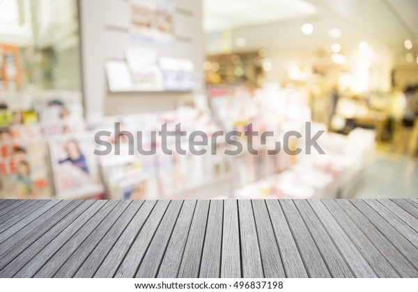 Empty top wooden table and blurred abstract background of a bookstore