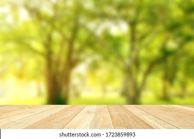 Empty top wooden table on blurred beautiful nature with green trees in park