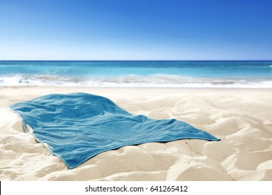 Empty towel on sand and free space