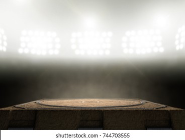 An empty traditional sumo wrestling ring made with sand lit by arena spotlights on a dark background - 3D render