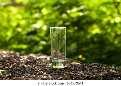 Empty transparent cylindrical glass over wooden table at restaurant, outdoor terrace, extreme shallow of depth field,space for copy text