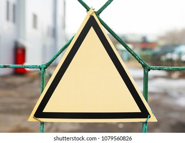 An empty triangular warning sign on the mesh fence.