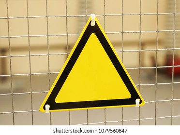 Empty triangular yellow sign on a mesh fence.
