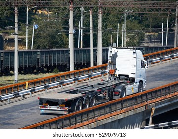 empty truck on road, rides up over the bridge, industrial infrastructure and railroad in sea port, cargo transportation, delivery and shipping concept