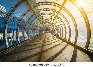 Empty tunnel with footpath lit by sunset