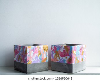 Empty two modern geometric concrete planters on white shelf isolated on white background with copy space. Beautiful painted concrete pots.