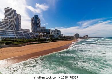 Empty Umhlanga beach shoreline ocean and waves against blue sky City skyline coastal landscape in Durban, South Africa