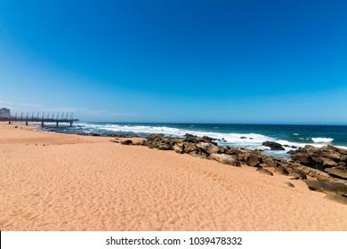 Empty Umhlanga Rocks beach and sea against blue sky coastal landscape in Durban, South Africa
