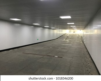 Empty underground pedestrian pathway with lights on. Modern tunnel with nobody at nice perspective.