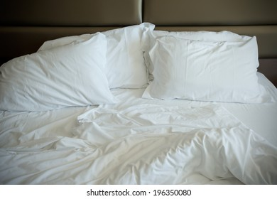 Empty unmade bed in a modern bedroom