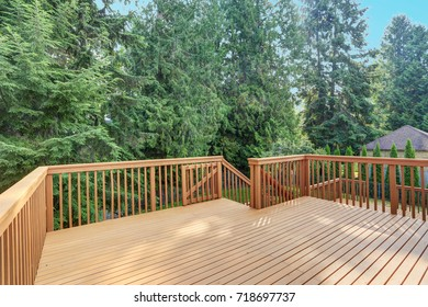 Empty upper level deck boasts redwood railings overlooking the lower level deck.