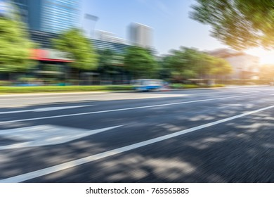 Empty urban road and modern buildings under blue sky