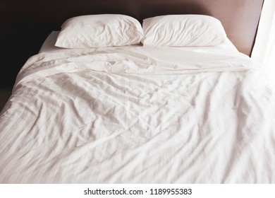 Empty Used Bed In The Bedroom With Two Pillows.