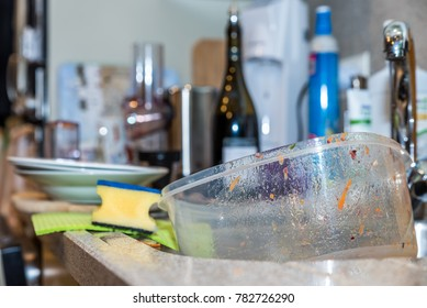 Empty used dirty plastic food container box in kitchen washing sink