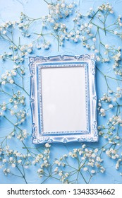 Empty  vintage frame and  fresh white gypsofila  flowers on blue textured background. Top view. Flat lay. Place for text. Vertical image.