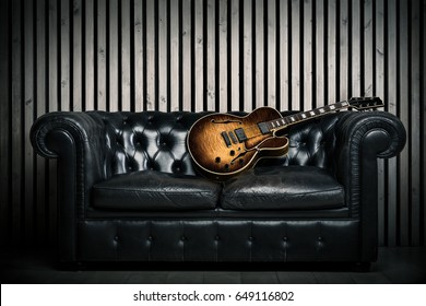 Empty Vintage Sofa And Electric Guitar With Modern Wood Wall Recording Studio Background Music Concept