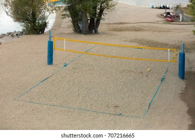 Empty volleyball beach court with a yellow net