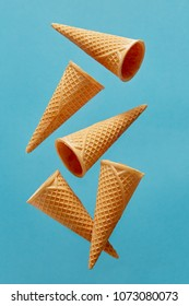 Empty Waffle Ice Cream Cones Against Blue Background