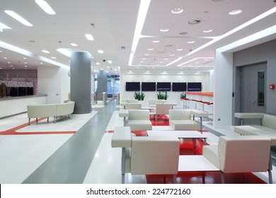 Empty waiting area with white chairs and plasma screens in a modern office