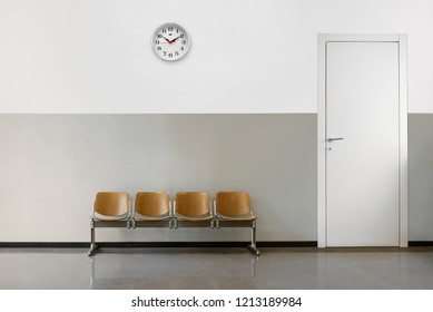 empty waiting room with chairs, clock on wall and door.