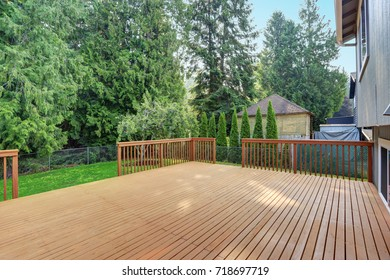 Empty walkout deck boasts redwood railings overlooking well kept back yard.