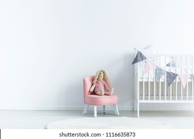 Empty wall next a to chair with a rabbit and crib with triangles on the rope in a baby room interior. Place your product