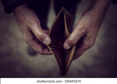 Empty wallet in the hands of an elderly man.