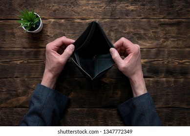 Empty wallet in hands on an office table background. No money concept. Debts. Bankruptcy.